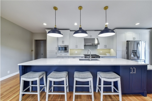 White shaker kitchen with deep blue shaker island ...